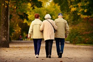 Woman walking with older parents in retirement community in New York